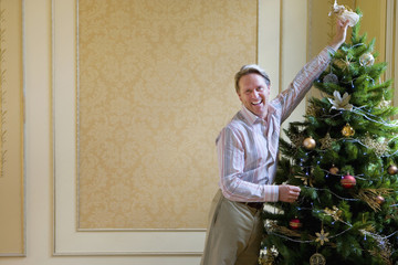 Mature man putting angel on top of Christmas tree, smiling, portrait