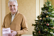Senior man with gift box by Christmas tree, smiling, portrait