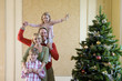 Family of four by Christmas tree, girl (4-6) with angel decoration on father's shoulders, portrait.