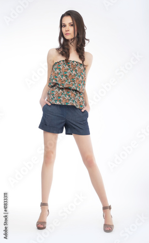 Elegant fashionable woman in shorts posing in studio