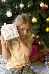Girl (5-7) holding gift to ear by Christmas tree, portrait