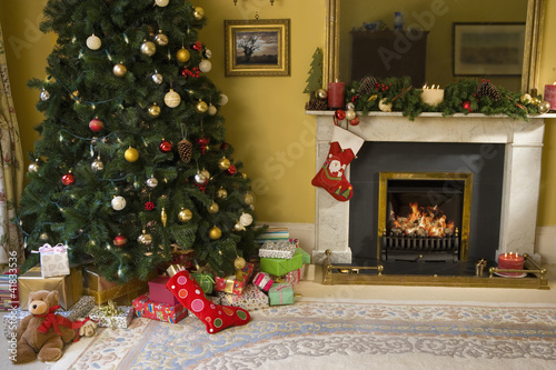 Christmas tree and gifts by fireplace