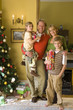Family of four with gifts by Christmas tree, father holding daughter (5-7), portrait