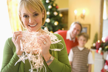Woman holding illuminated Christmas tree lights, smiling, portrait, husband and son (9-11) in background.