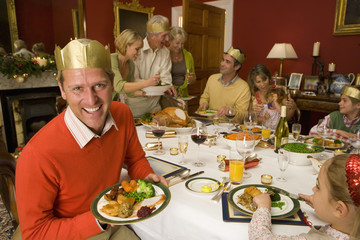 Family having Christmas dinner, portrait of man