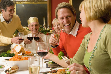 Family having Christmas dinner, portrait of mature man smiling