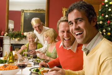 Family having Christmas dinner, portrait of men smiling