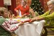 Family having Christmas dinner, grandmother pulling cracker with grandson (9-11)