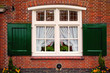 Old retro window with shutters on red brick house
