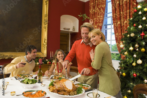 Family having Christmas dinner, woman embracing husband cutting turkey