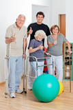 Disabled Senior People With Trainer Showing Thumbs Up Sign
