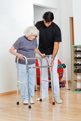 Trainer Assisting Senior Woman In Moving