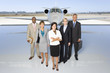 Small group of people in line behind woman by aeroplane on runway, portrait, elevated view