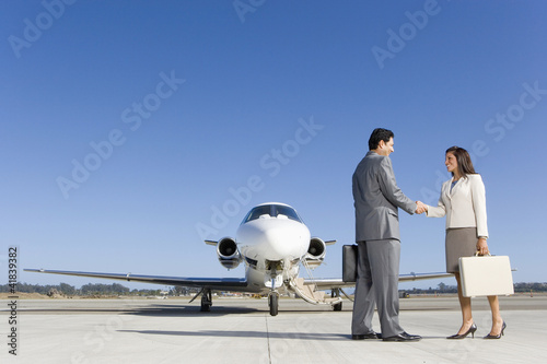 Businessman and woman with briefcase shaking hands by aeroplane on runway, low angle view