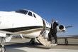 Businessman boarding aeroplane on runway