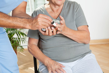 Male Nurse Checking Sugar Level Of Patient