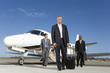 Businessmen by aeroplane on runway, low angle view