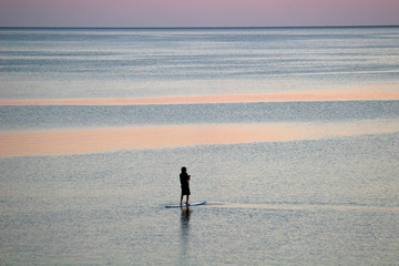 paddle boarder at dusk