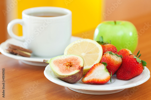 cup of tea,cookie,apple, lemon, fig and strawberries on a plate