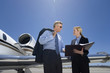 Businesswoman showing businessman in sunglasses folder by aeroplane on runway, low angle view