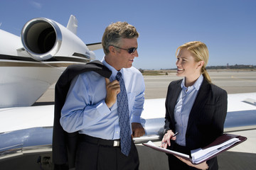 Businessman and woman looking at folder by aeroplane on runway, smiling, close-up