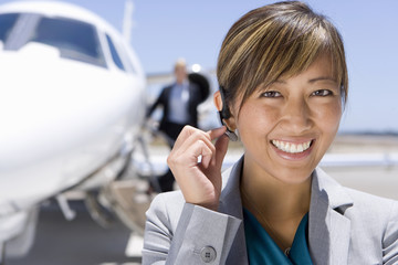 Businesswoman with hand on earpiece by man on aeroplane steps, smiling, portrait, close-up
