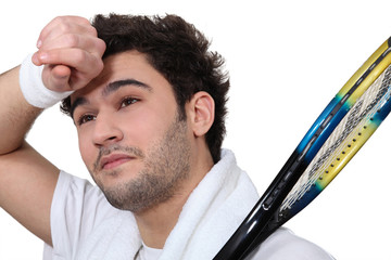 Tennis player wiping the sweat from his brow
