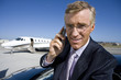 Businessman using mobile phone by car, on runway by aeroplane, smiling, portrait