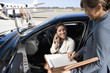 Businesswoman using mobile phone in car smiling by colleague with pen and folder, on runway by aeroplane