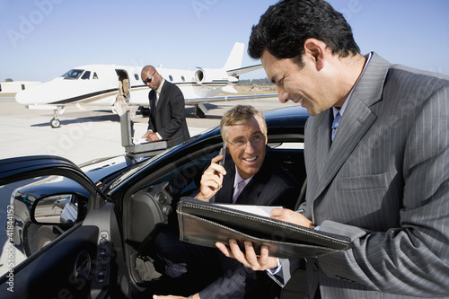 Businessman using mobile phone in car smiling at colleague with folder, on runway by aeroplane