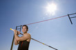Young male pole vault athlete with pole by bar, portrait, low angle view (sun flare)