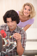 Couple repairing their television