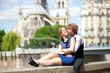 Romantic summer day in Paris, couple of tourists sitting by Notr