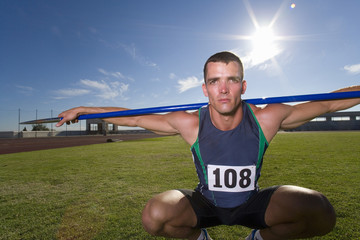Male athlete crouching with javelin over shoulders, portrait (lens flare)