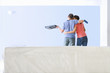 Couple with paint roller and tray kissing and looking at freshly painted living room wall