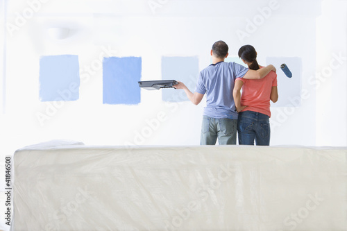 Couple holding paint roller and tray and examining blue paint samples on living room wall