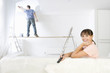 Woman smiling on sofa as man paints living room wall in background on wood plank