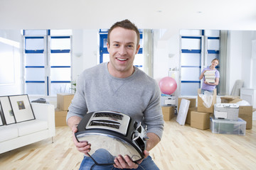 Smiling man holding toaster as woman unpacks in living room