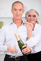 Smart senior couple with bottle of champagne