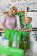Teacher and student sorting recyclables together in classroom