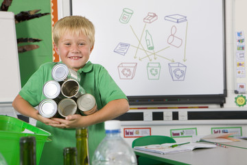 Smiling student holding recyclable tin cans in classroom