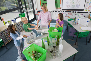 Teacher and students sorting recyclables in classroom