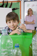Smiling student putting glass into recycling bin