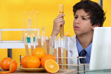 Boy analysing orange juice