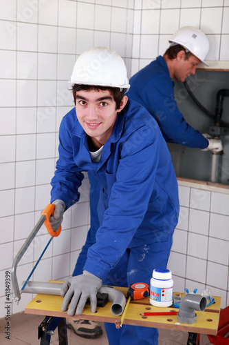 Young plumber cutting plastic pipe