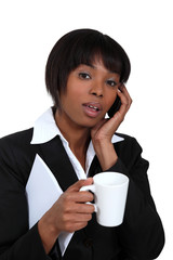 Businesswoman with mug of coffee and telephone