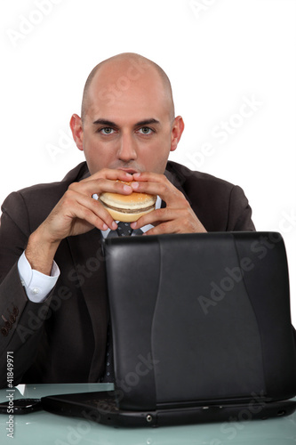 Businessman eating a burger at his desk