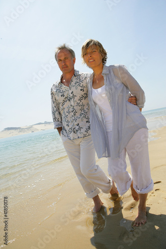 Romantic couple walking barefoot along a beach