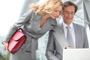 Business couple looking at laptop