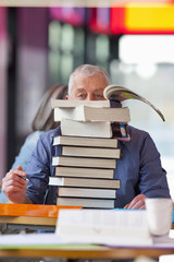 Overwhelmed mature student sitting behind stack of textbooks